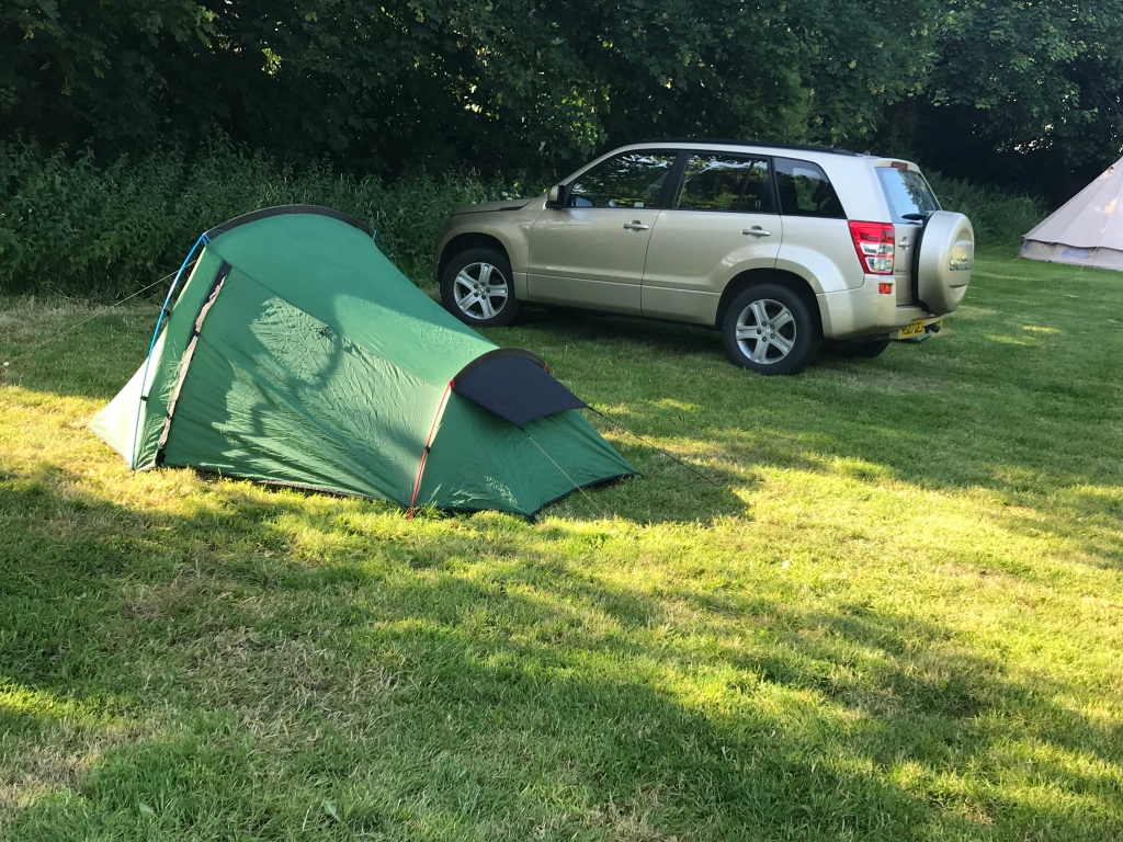 A picture of  my tent  erected at the side of a golden car