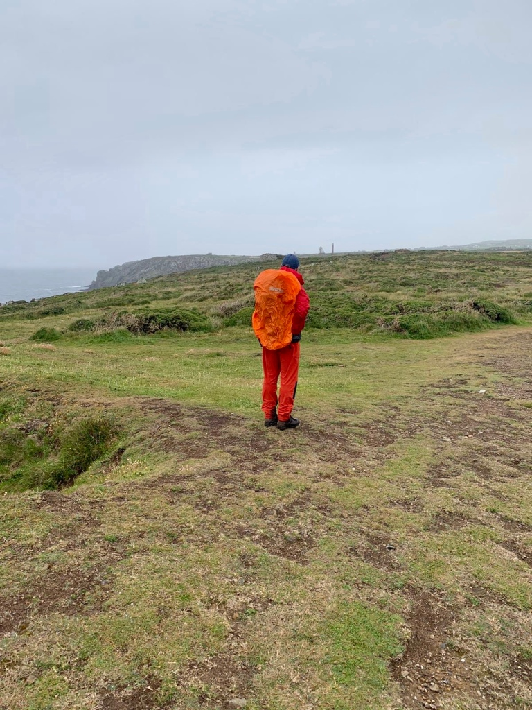 A picture of me wearing my waterproof  clothing stood over looking the Southwest Coastal path looking out to Cape Cornwall